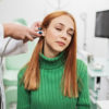Young adult redhead woman at medical examination or checkup in otolaryngologist's office